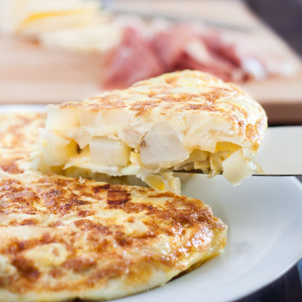 Tortilla Espanola - Spanish Tortilla - is a classic egg and potato dish with infinite variations served all over Spain and in some parts of the Caribbean. An easy budget meal, tortilla can be served any time of day, or cut into cubes and served as a party appetizer! Recipe and variations on GoodieGodmother.com