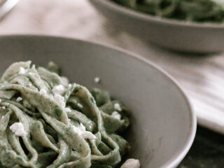 offset photo of prepared fresh spinach pasta in low grey bowls, cut into a thick noodle shape