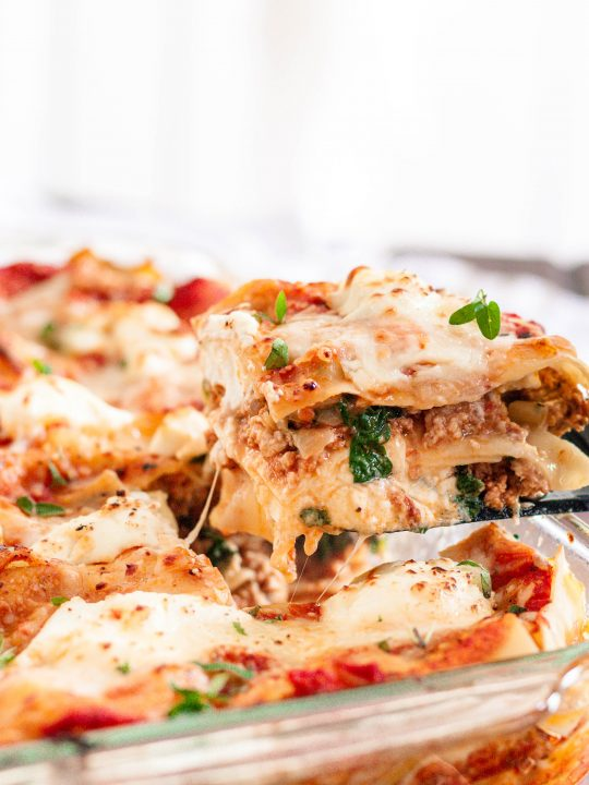 spatula lifting a slice of the turkey spinach lasagna out of the dish with stringy cheese!