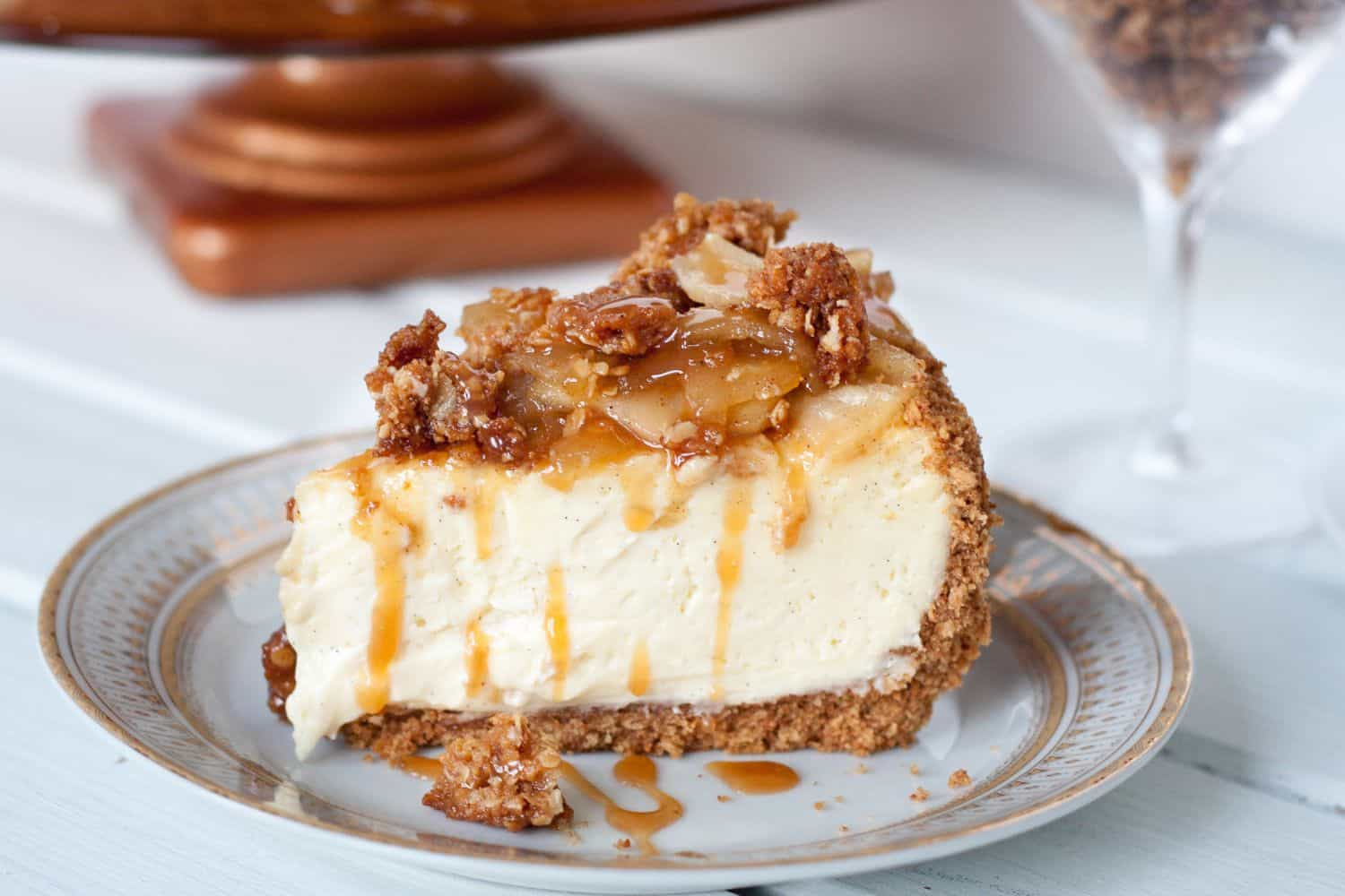 Caramel Apple Cheesecake - A creamy vanilla bean cheesecake on a cinnamon graham crust topped with a homemade apple pie filling, a crunchy streusel topping, and liberally drizzled with caramel sauce! Get the recipe on GoodieGodmother.com