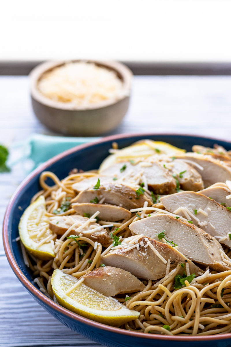 lemon chicken pasta ready to be served family style in a blue bowl set on a table near a window
