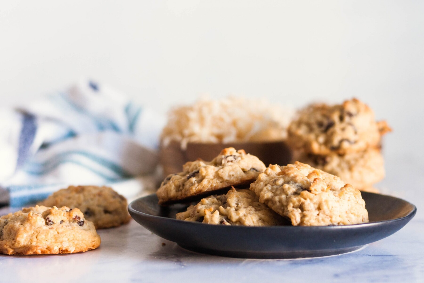 coconut oatmeal cookies on a black plate with a bowl of shredded coconut and a white and blue napkin in the background