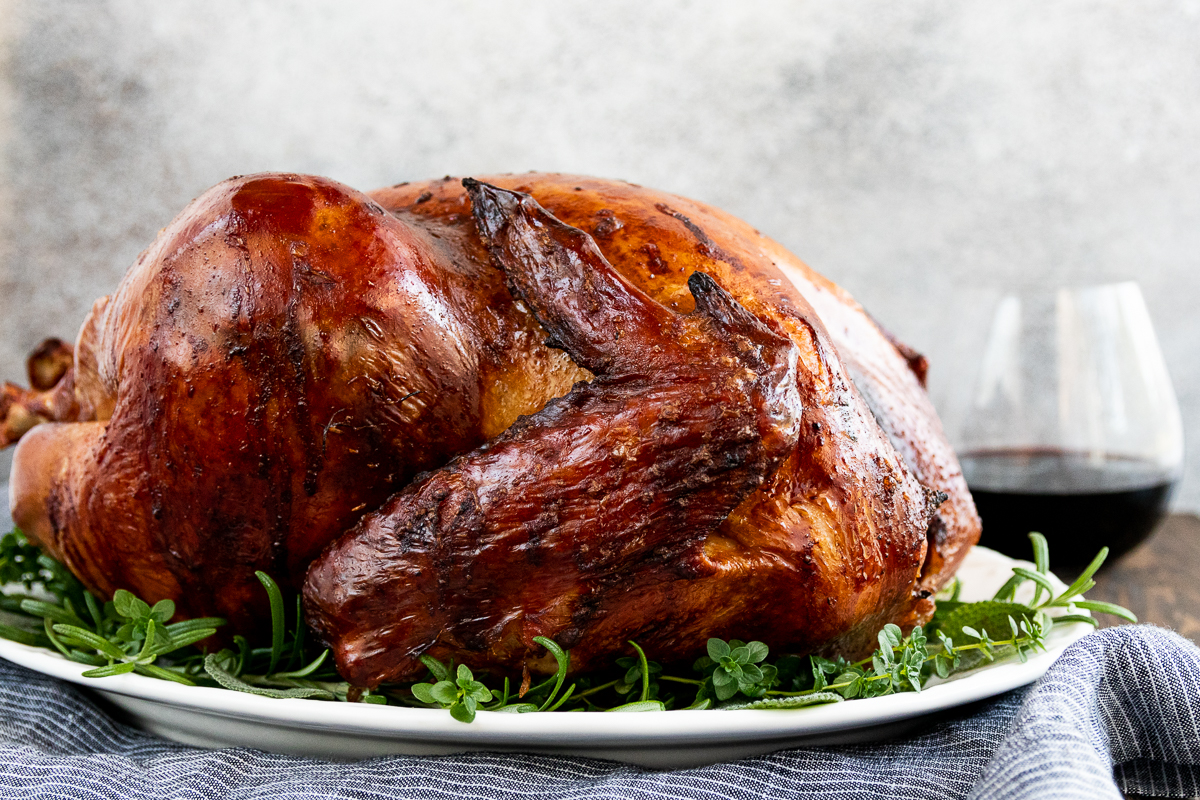 golden brown smoked thanksgiving turkey on a white platter surrounded by a fresh herb garnish