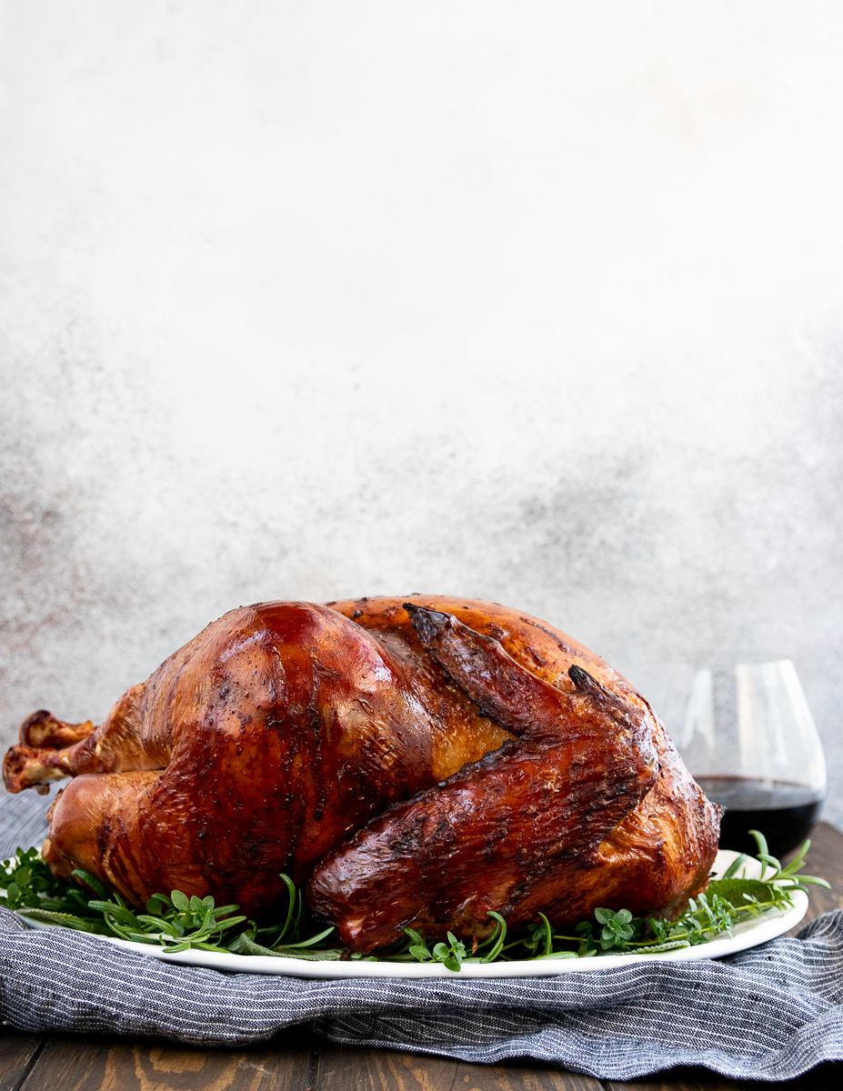 side view of a whole thanksgiving turkey on a white platter sitting on a grey pinstripe napkin with a glass of pinot noir in the background