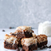 dulce de leche coconut brownies stacked on a white plate