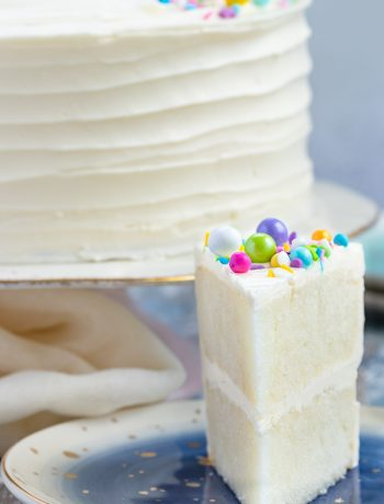 Naturally white, and easy to mix up with no special ingredients required, this white cake recipe from scratch is moist and delicious! Put down the box mix, and make white cake from scratch at home.* Recipe on GoodieGodmother.com #whitecake #weddingcake #birthdaycake #vanillacake