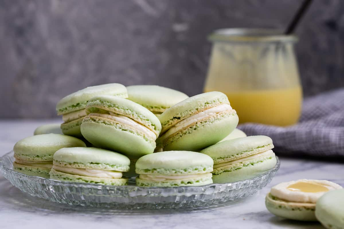 Key lime macarons are filled with a key lime buttercream and key lime curd. Lots of key lime flavor packed into every naturally gluten-free macaron bite! * Recipe on GoodieGodmother.com