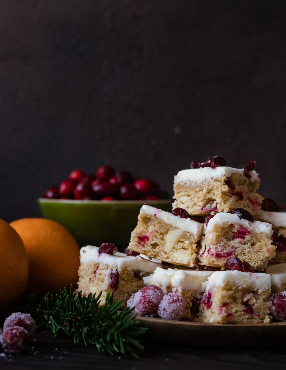 Fresh cranberry orange cookie bars on a plate with cranberries and oranges in the background