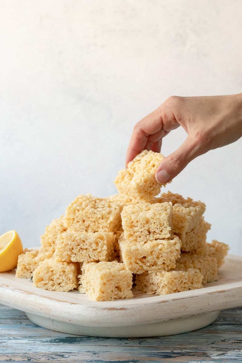 hand reaching to grab the top lemon cereal treat off the stack on the platter