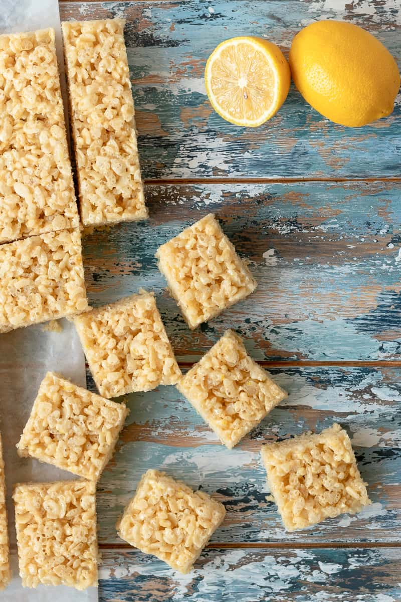 flat lay photo of the lemon cereal treats on a blue mottled background with a sliced lemon in the upper right corner and scattered squares on the lower left