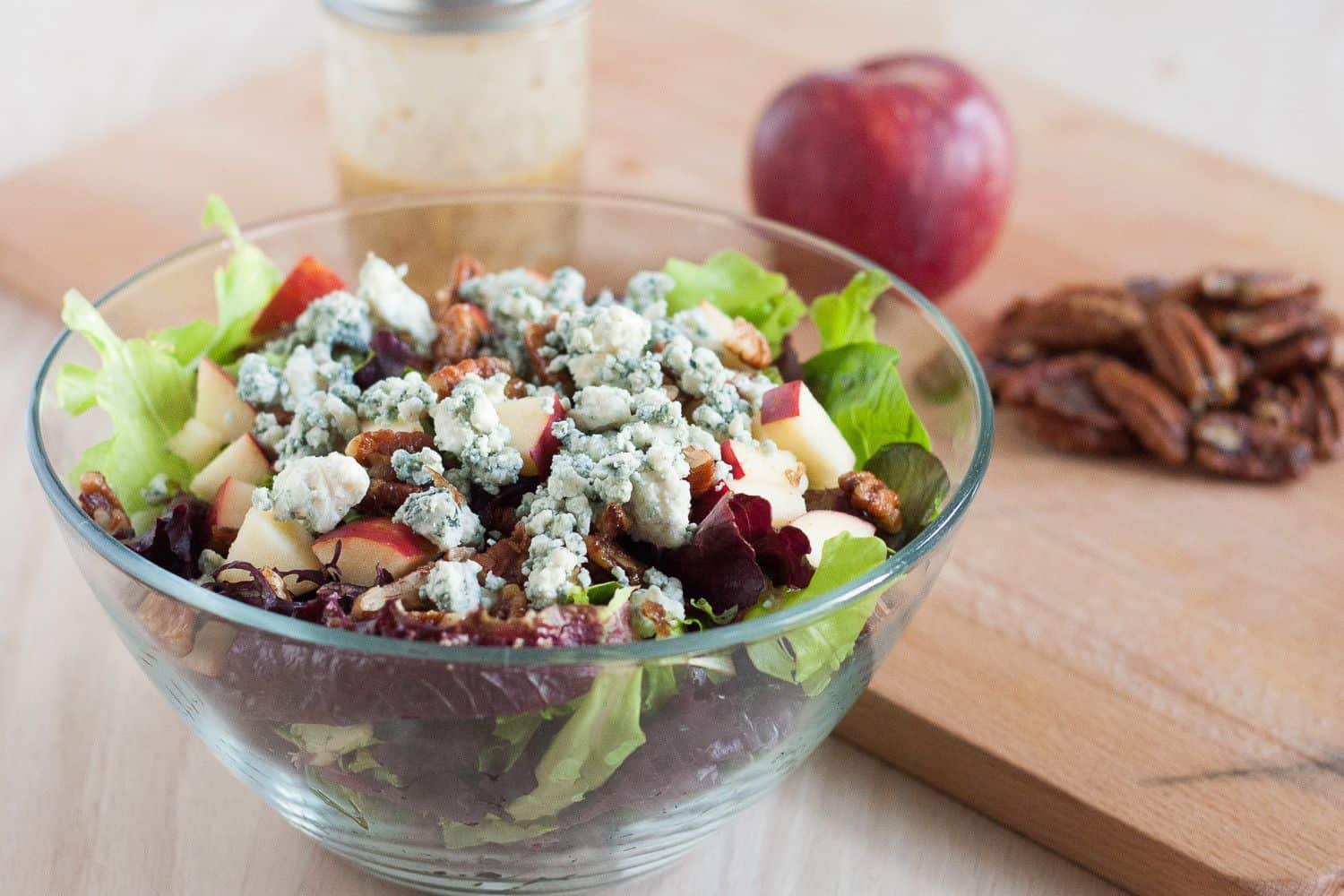 This salad is perfect for fall! Blue cheese crumbles, quick candied pecans, fresh apples, dark leafy greens, and an easy red wine vinaigrette. It's healthy fall comfort food!