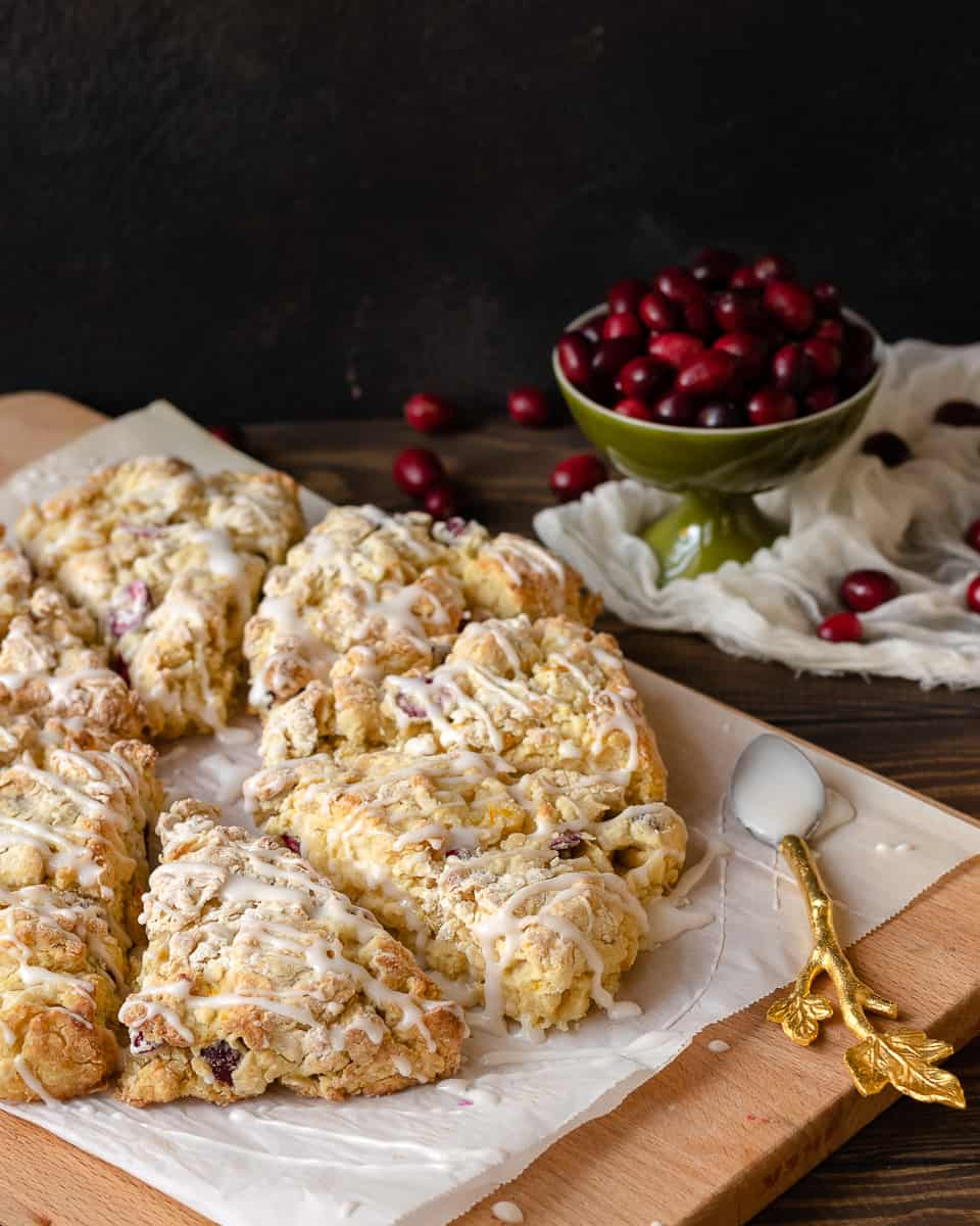 Keep winter breakfast bright with these flavorful fresh cranberry orange scones! Make the dough ahead and freeze, or mix and bake in under an hour. This easy buttermilk scone recipe is a great way to use fresh cranberries! * Recipe on GoodieGodmother.com