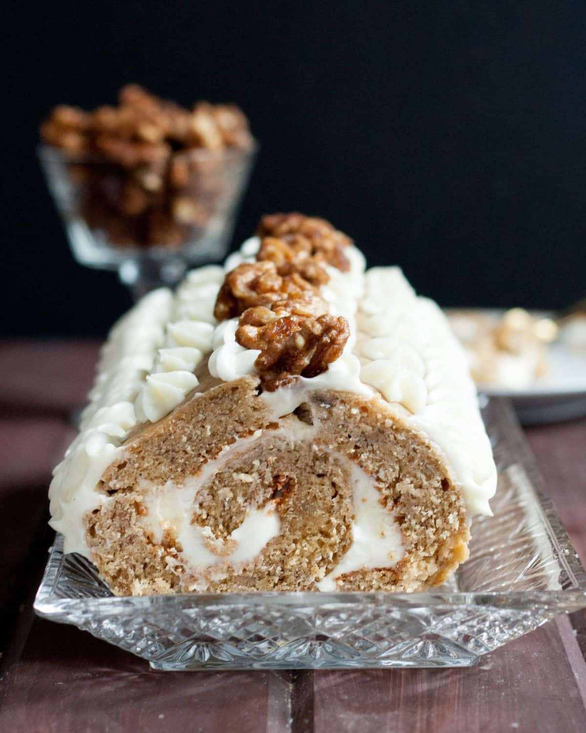 A new way to eat banana bread! Traditional banana bread turned into a roll cake, filled with cream cheese frosting, and topped with balsamic glazed walnuts. Recipe on GoodieGodmother.com
