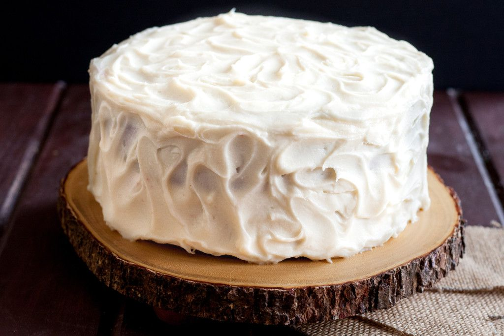 horizontal image of a red velvet cake with cream cheese frosting, unsliced, on a wooden cake board