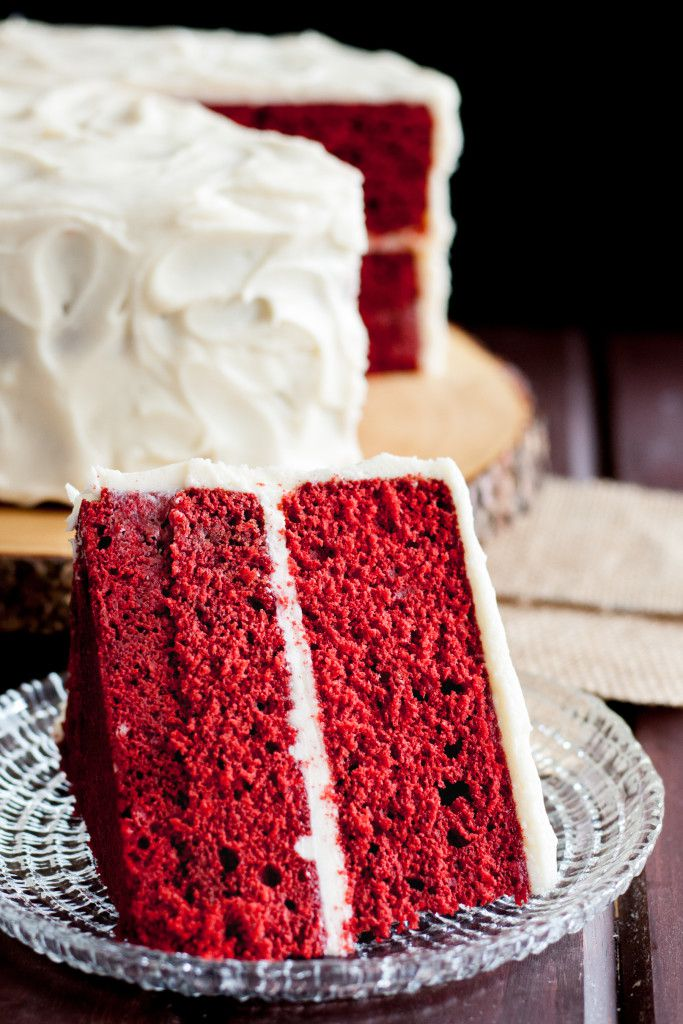 Vertical red velvet cake image showing a slice of red velvet cake on its side on a glass plate in the foreground of the image. You can see the blurred cake with a slice taken out in the background.