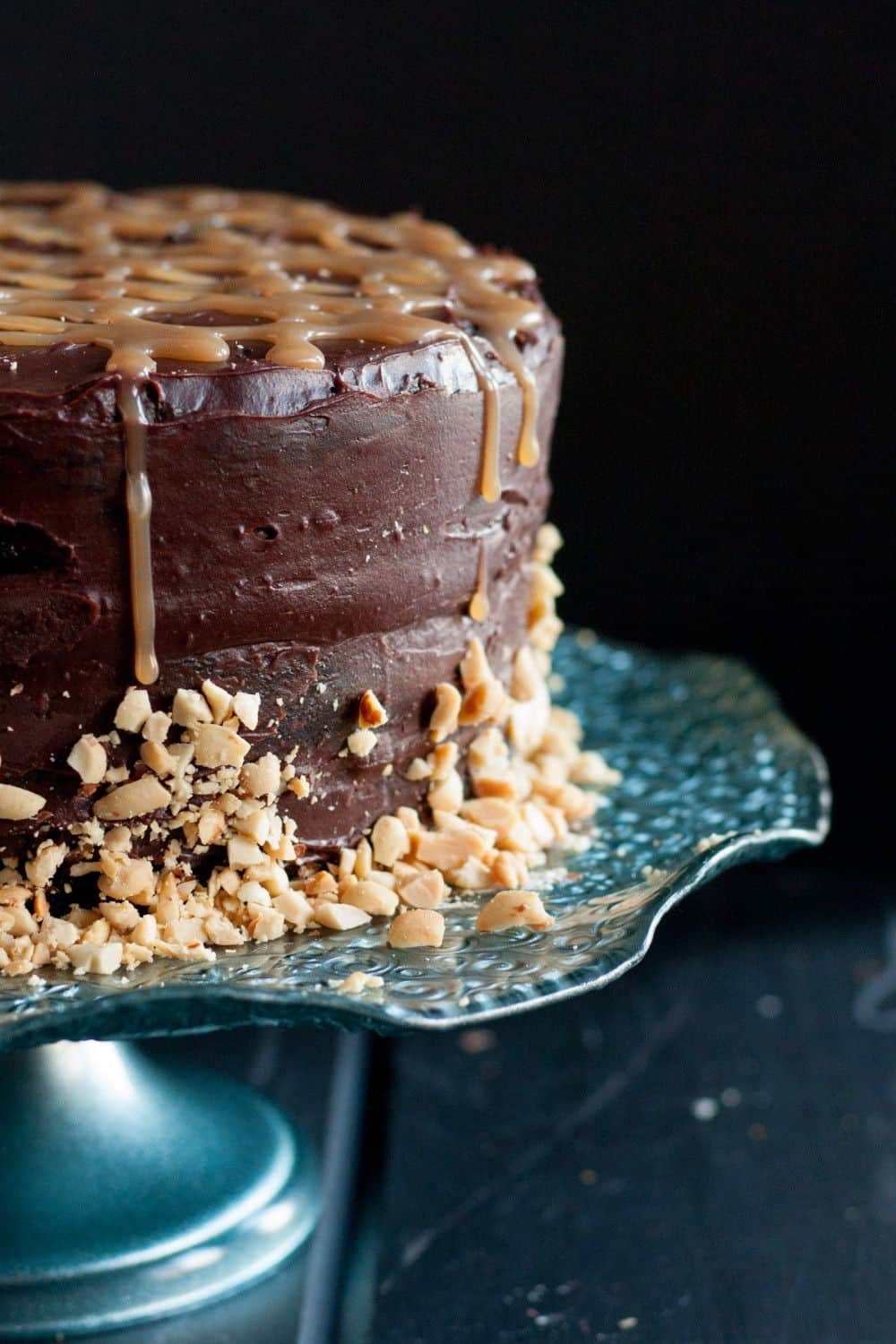 Rich chocolate cake, layers of homemade nougat, peanuts, and caramel, all covered with a rich ganache - candy bar dreams come to life! Recipe on GoodieGodmother.com