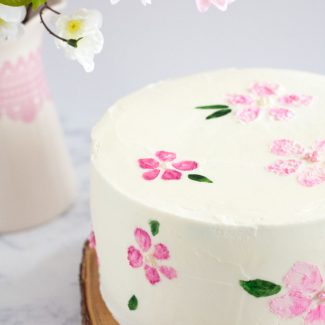 Check out this cherry blossom cake tutorial to learn how to decorate a cherry blossom cake by painting on buttercream! Tutorial, FREE stencil printable, and video on GoodieGodmother.com