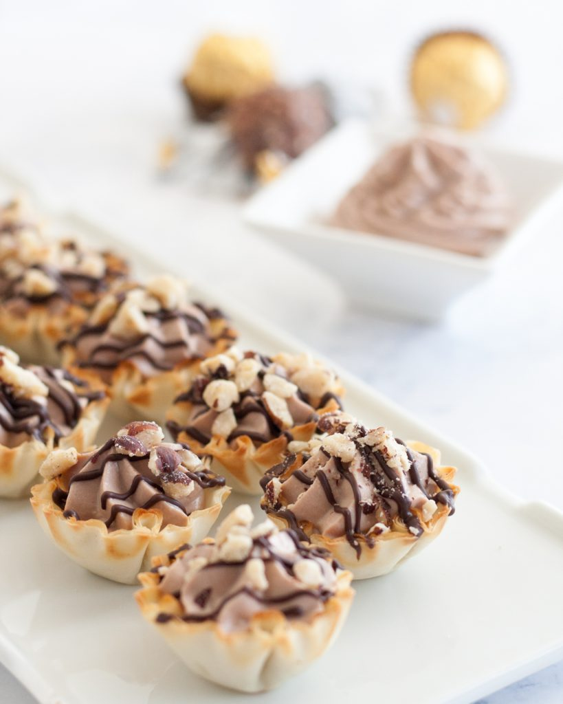 Easy Ferrero Rocher Cannoli Cups - This easy bite size dessert comes together in just a few minutes and is always a hit at parties! * Recipe on GoodieGodmother.com
