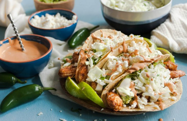 """A healthy and easy shrimp taco recipe that your whole family will enjoy! Grilled chipotle shrimp with cilantro sauce and cabbage slaw topped with your choice of avocado salsa or queso. Pair it with low carb or gluten free tortillas for an """"extra"""" healthy meals. #shrimptacos #cabbageslaw #cilantrolimesauce #chipotle #tacorecipe"""