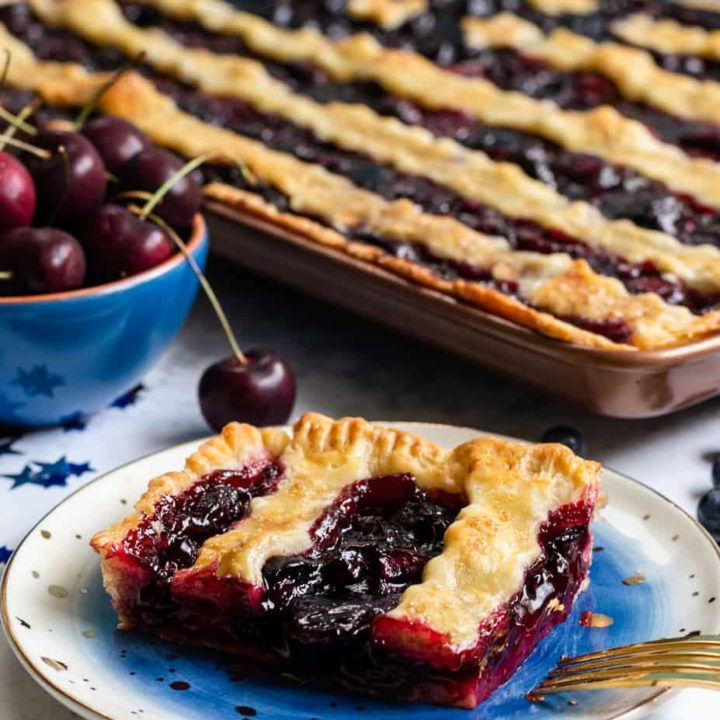 This patriotic blueberry cherry slab pie is a festive way to celebrate summer. Even pie newbies will achieve beautiful results with the easy to follow video tutorial!* Recipe on GoodieGodmother.com #4thofjuly #patrioticdessert #redwhiteandblue #slabpie #cherrypie #summerdessert