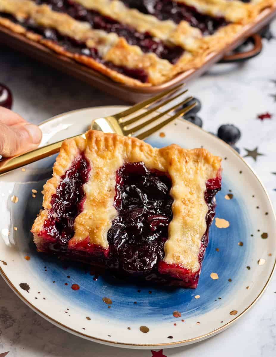 This patriotic blueberry cherry slab pie is a festive way to celebrate summer. Even pie newbies will achieve beautiful results with the easy to follow video tutorial! * Recipe on GoodieGodmother.com #4thofjuly #patrioticdessert #redwhiteandblue #slabpie #cherrypie #summerdessert