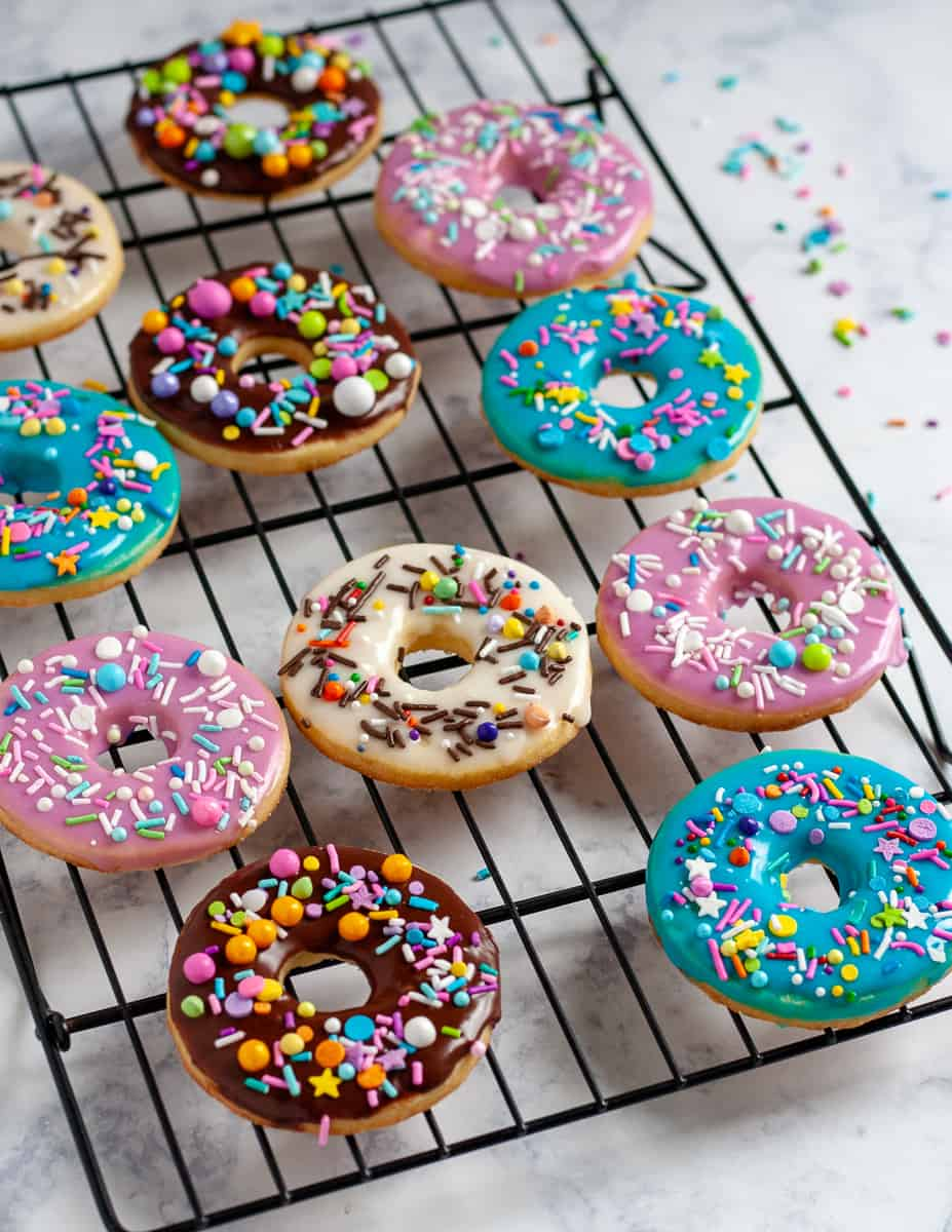 Whip up a batch of colorful iced sugar cookies in no time with this doughnut sugar cookie tutorial and easy cookie glaze recipe! It's so easy to make these colorful cookies - even if you've never decorated a sugar cookie before. * GoodieGodmother.com