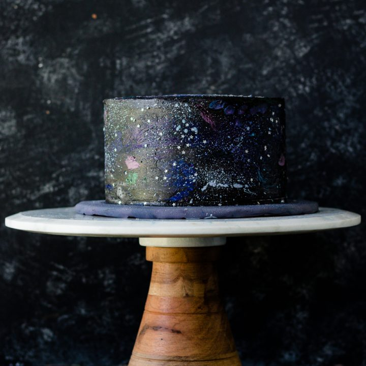 Decorate your own out of this world cake with this easy to follow buttercream galaxy cake decorating tutorial! Video and all the details on GoodieGodmother.com