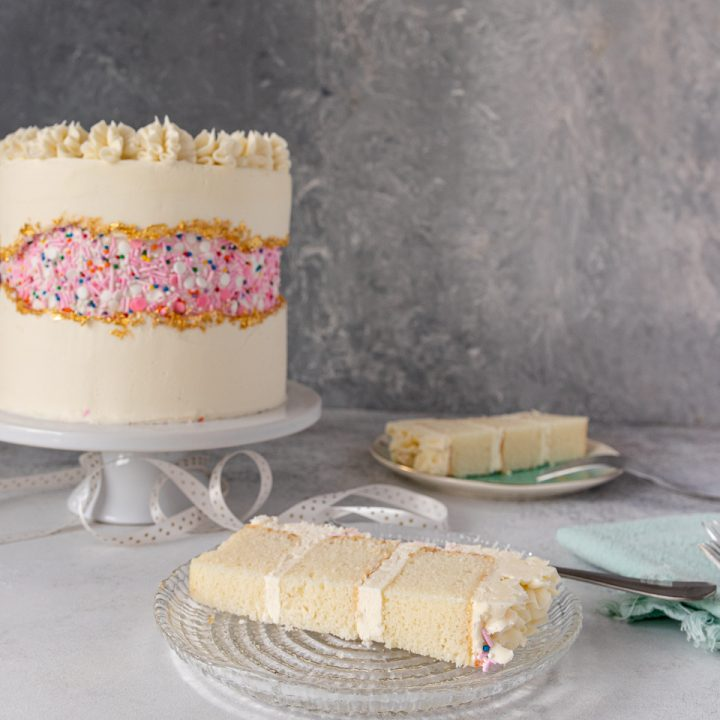 Slice of moist vanilla cake with whole cake in background