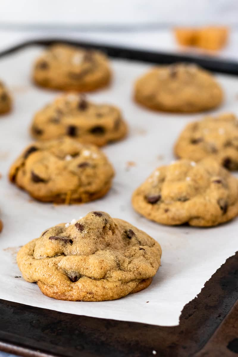 caramel stuffed chocolate chip cookies resting on a baking sheet lined with parchment