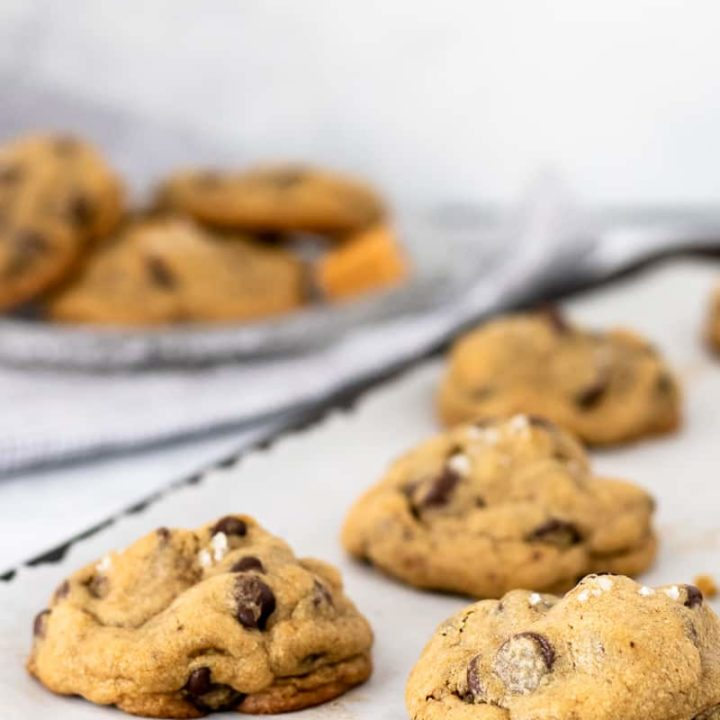 salted caramel mocha chocolate chip cookies on a baking sheet with a small plate in the background