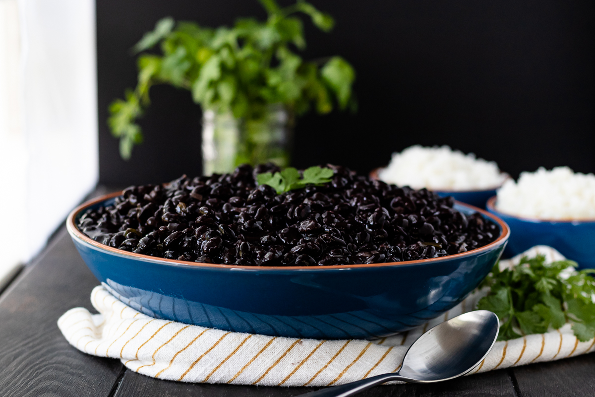 landscape picture of black beans in a bowl with spoon in the foreground