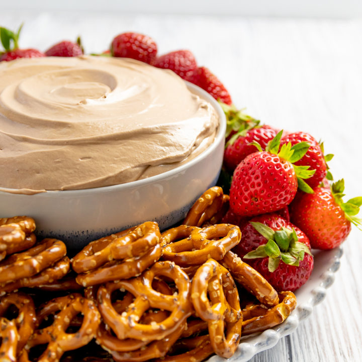 close up picture of Nutella fruit dip in a bowl with pretzels and strawberries
