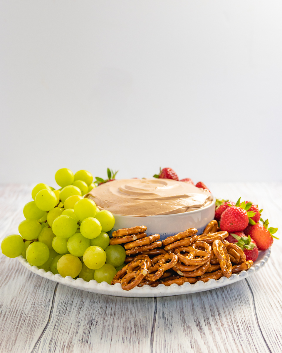 easy fruit dip serving suggestion on a white platter with white background