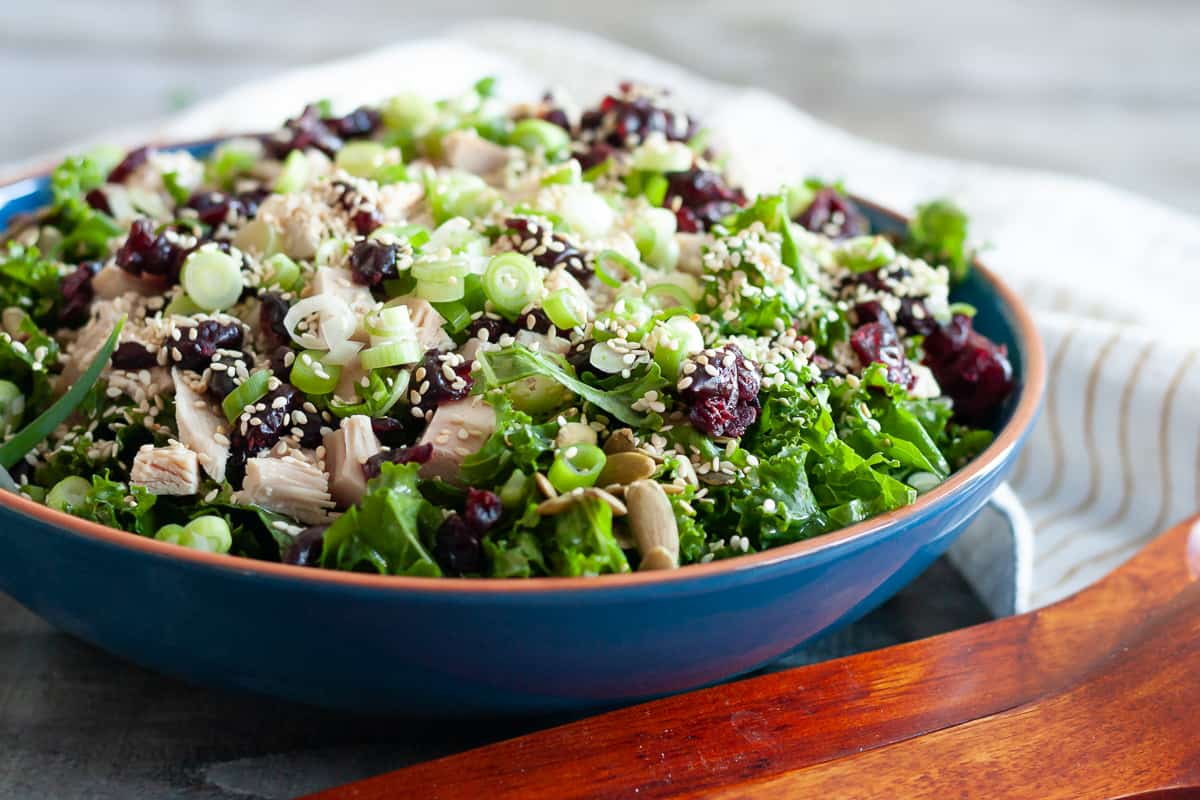 turkey kale salad in a blue bowl with serving utensils