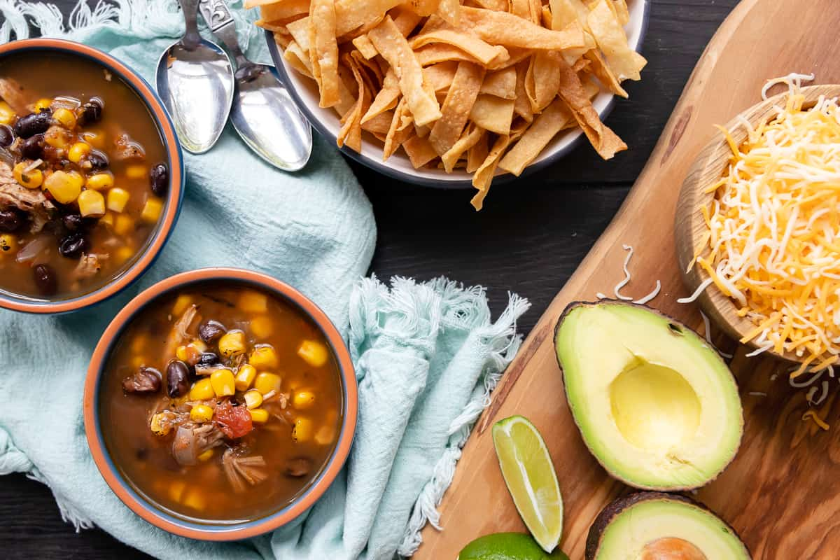 landscape flat lay photo showing turkey tortilla soup with optional toppings on the side. bowls are on a light blue napkin with frayed edges