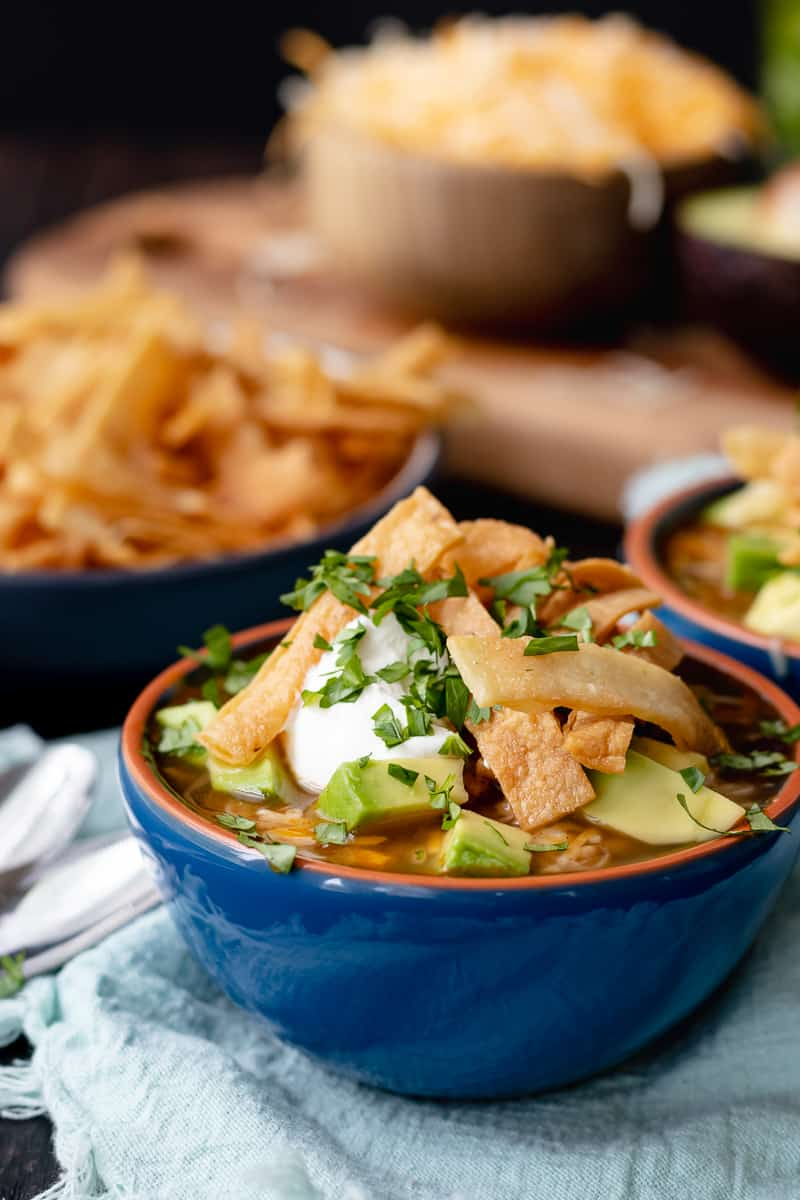turkey tortilla soup with all the toppings in a blue bowl