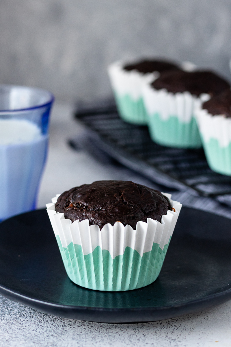 chocolate greek yogurt muffin on a black plate ready to serve in a white and aqua paper muffin liner