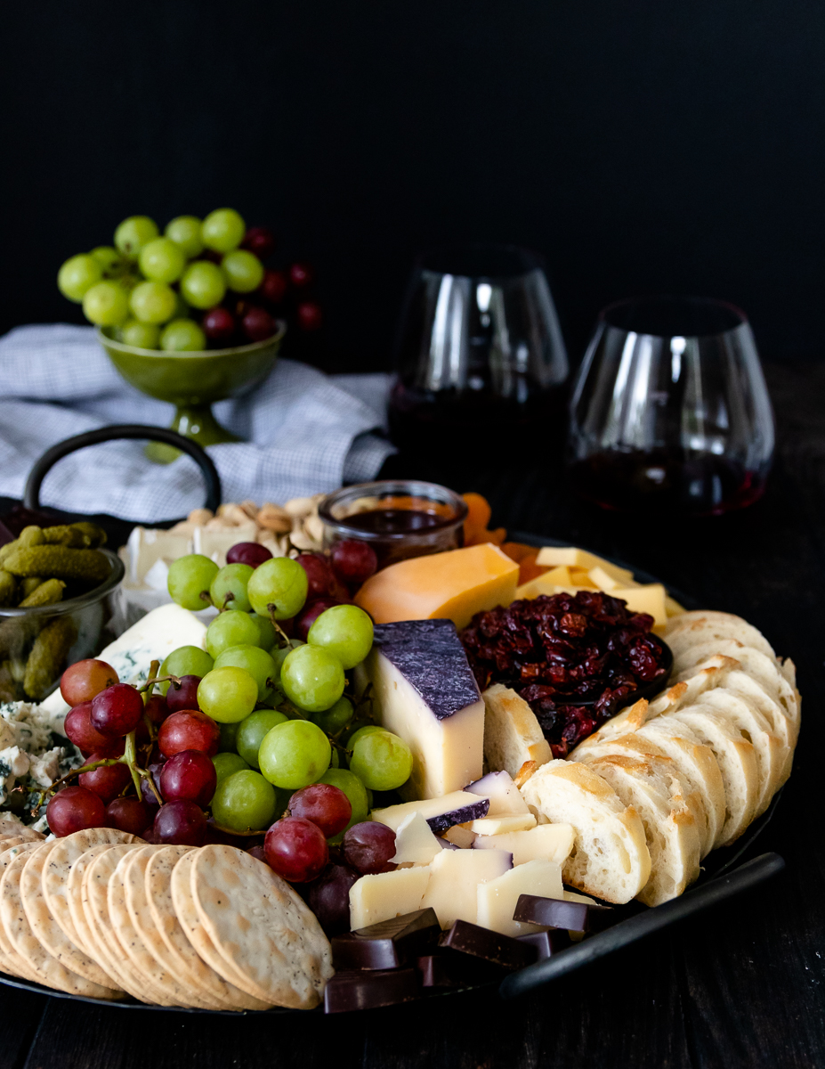round cheese board with grapes, bread, and crackers. Wine glasses in the background