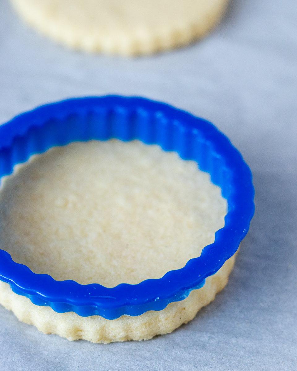 angled picture of the no chill sugar cookie recipe to show it doesn't spread. A blue circle cookie cutter with fluted edges sitting on a baked sugar cookie