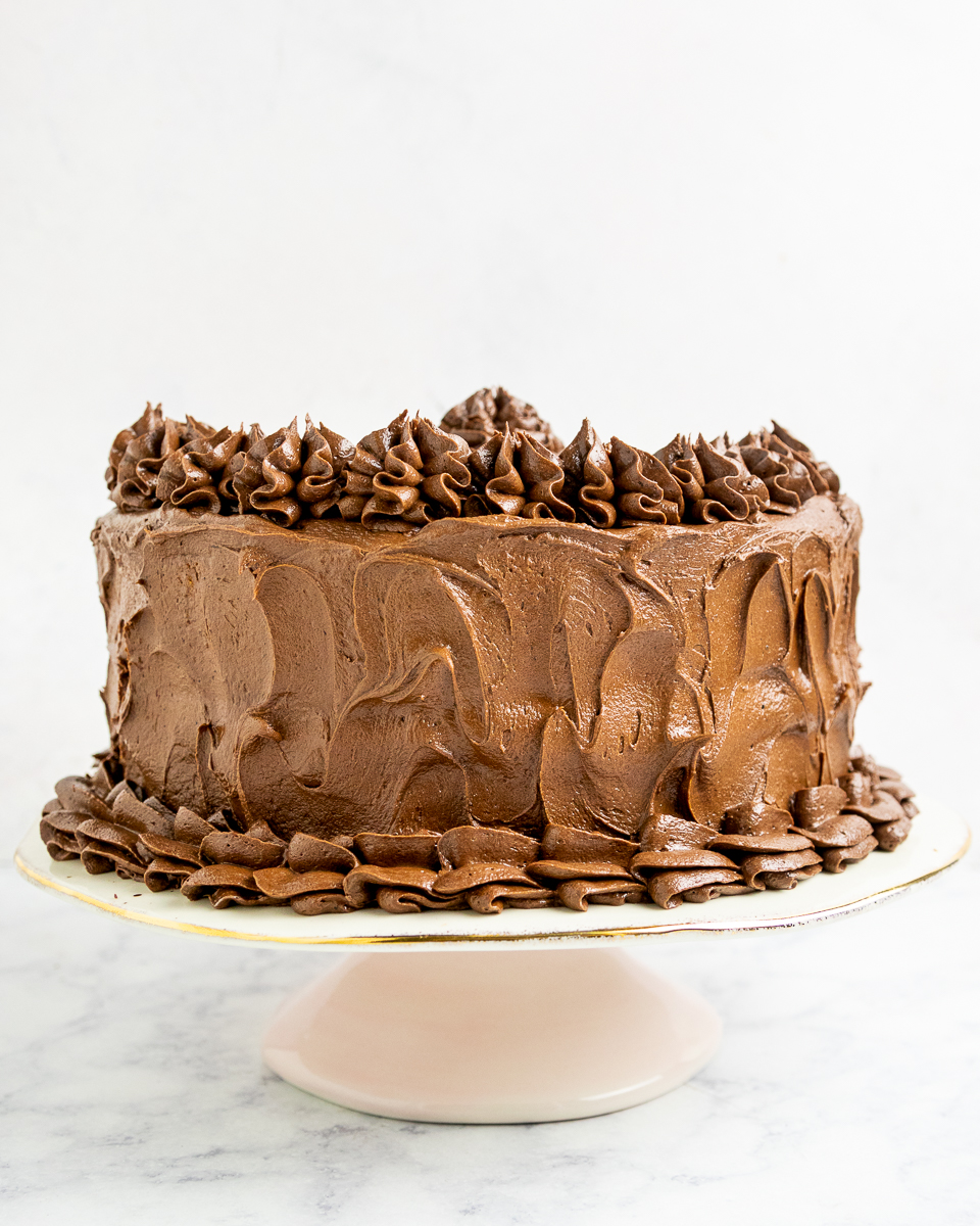 cake with no cook fudge frosting on a light pink cake stand