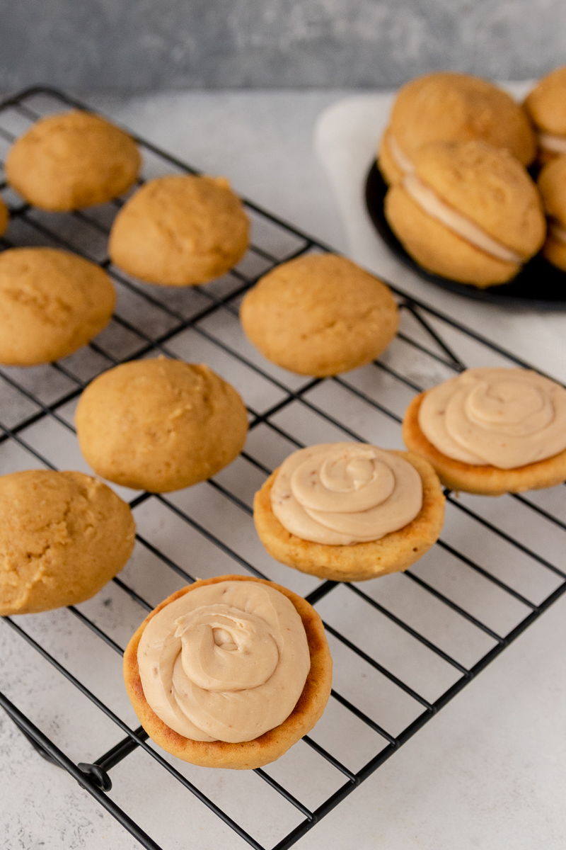pumpkin whoopie pies half filled on a cooling rack to show approximately how much frosting I used per cookie sandwich