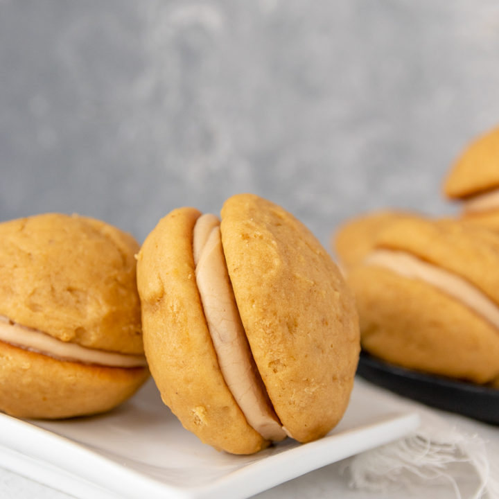 close up of the pumpkin whoopie pies to show layers. pies arranged on a white plate with a grey mottled background