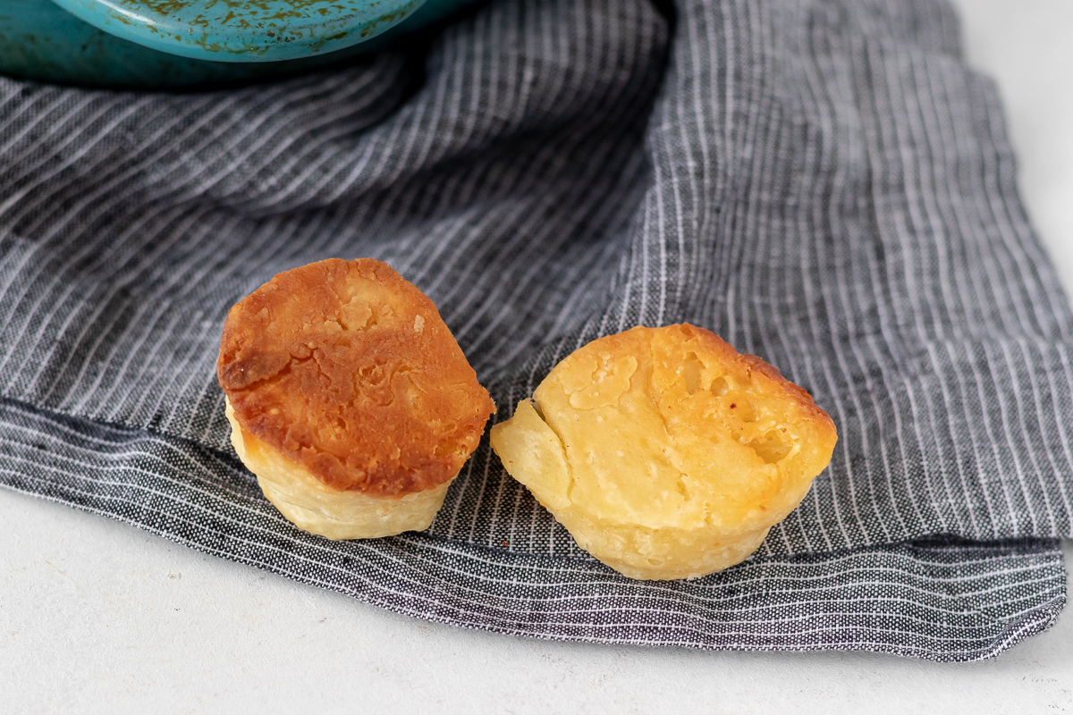 two upside down biscuits on a grey pinstripe napkin. The one on the left was baked in cast iron and has a darker bottom and the one on the right was baked in a glass dish.