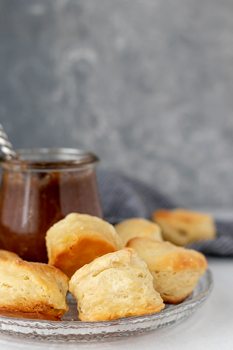 flaky homemade biscuits on a plate with apple butter (serving suggestion)
