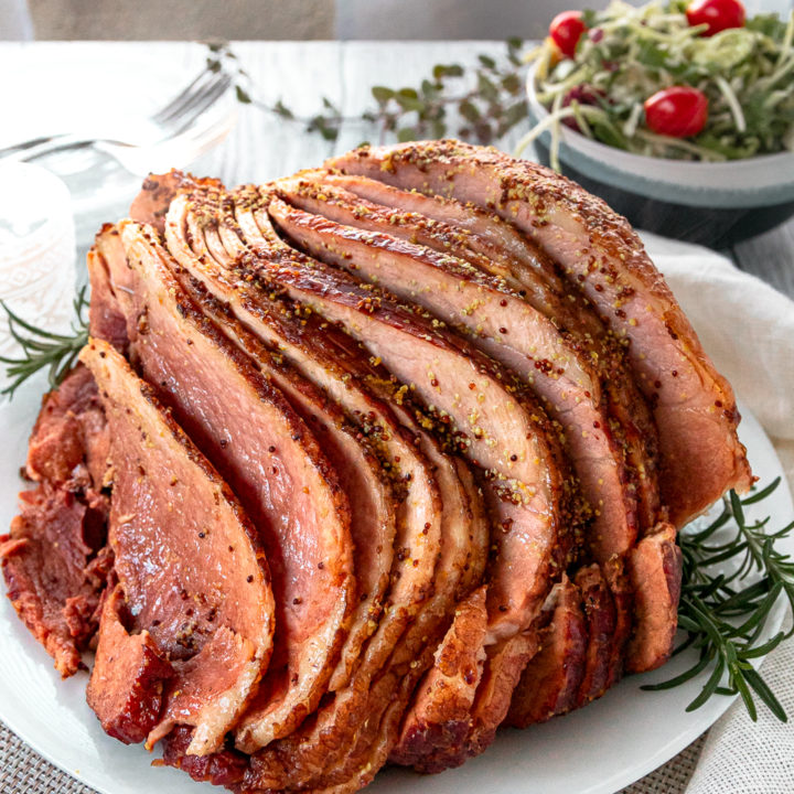 coca-cola slow cooker ham on a white platter garnished with rosemary