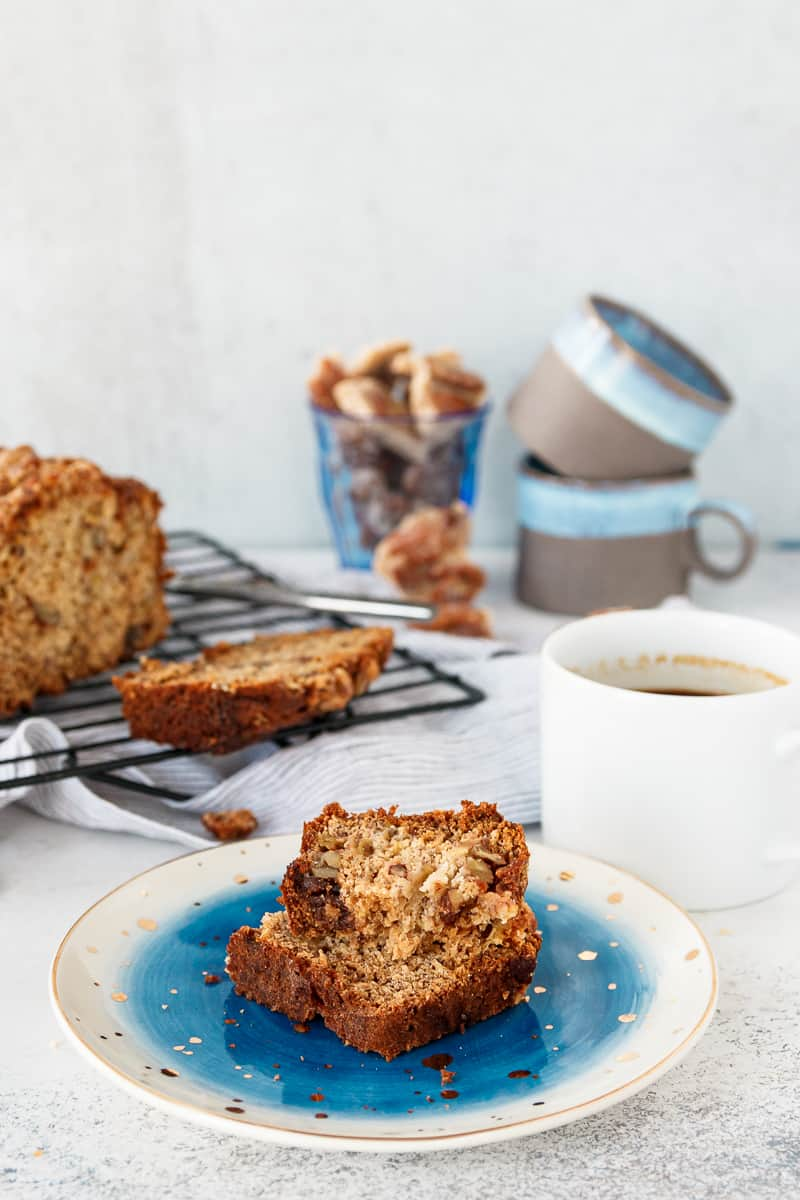 slice of praline banana bread stacked on a serving plate near coffee cups. A serving suggestion