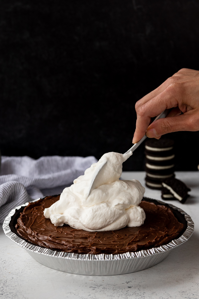 adding whipped cream to the chocolate pudding pie