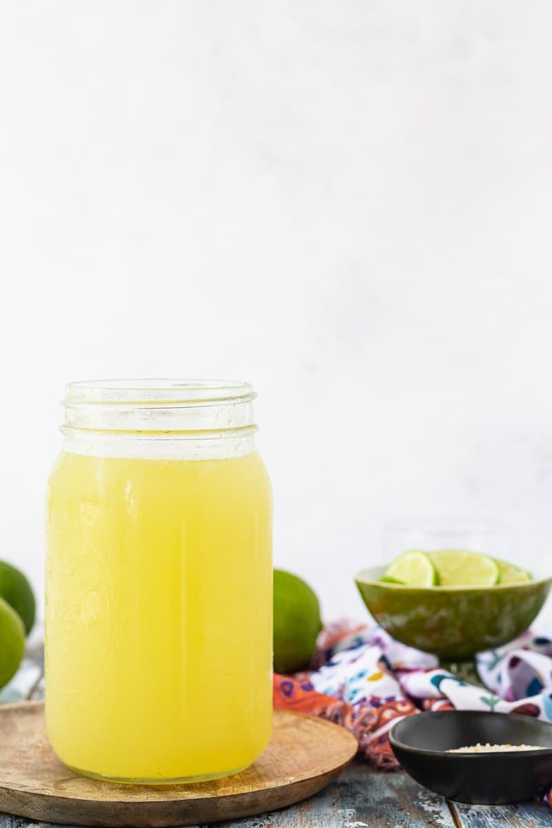 the best margarita mix recipe, diy sweet and sour mix. Shown in a large mason jar for storage.