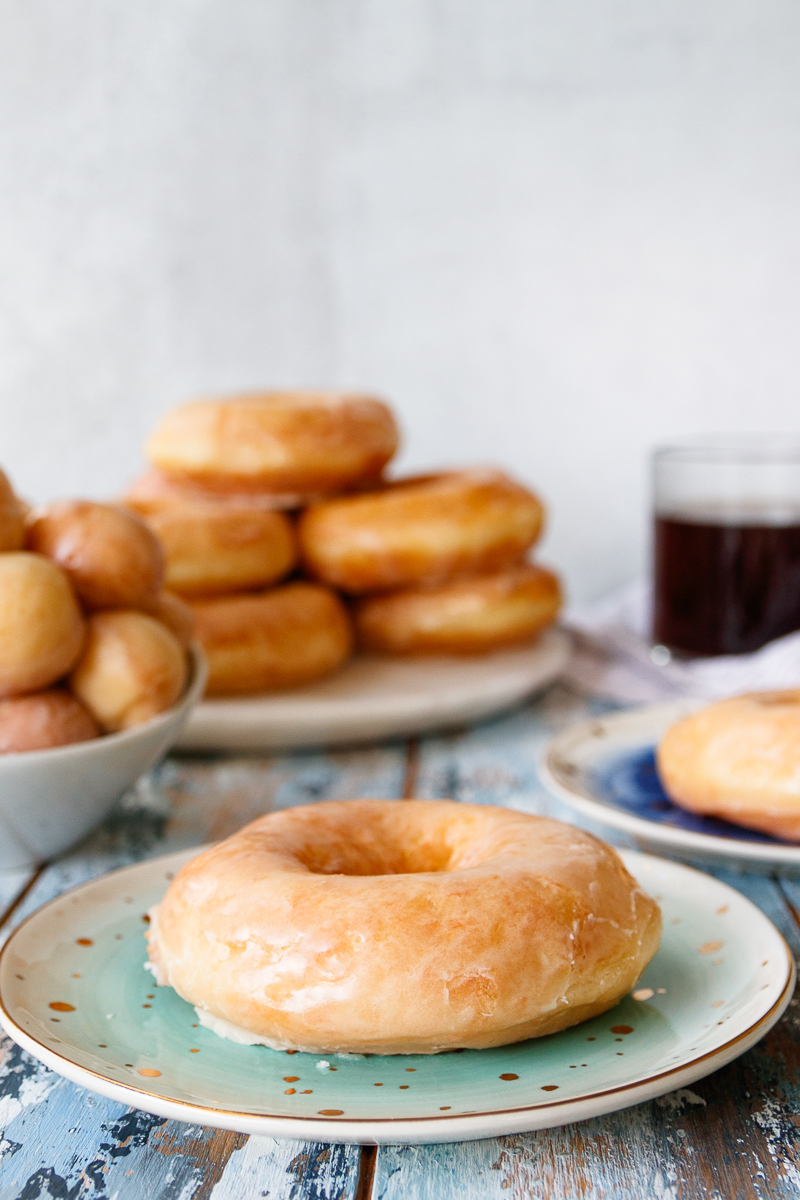 glazed sourdough doughnut on a plate with a stack of doughnuts and donut holes in the background