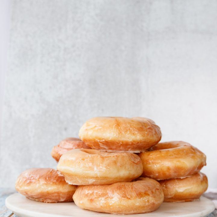 sourdough discard donuts stacked on a white marble tray with a light grey background